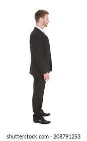 Full length side view of mid adult businessman standing isolated over white background