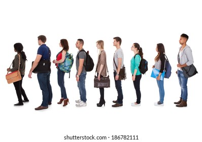 Full length side view of multiethnic college students standing in a row against white background