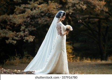 Full length side view of one beautiful sensual young brunette bride in long white wedding dress and veil standing in forest holding bouquet outdoor on natural background, horizontal picture