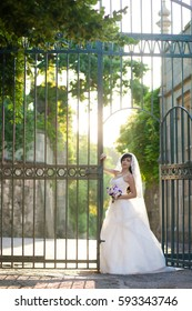 Full length side view of one beautiful sensual young brunette bride in long white wedding dress and veil standing in forest holding bouquet outdoor on natural background