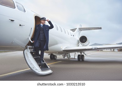 Full length side view outgoing pilot standing on stairs of aircraft. Profession concept