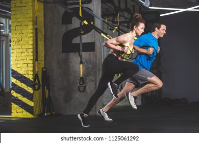 Full length side view outgoing male and concentrated girl doing exercise with functional loops. They situating in gym