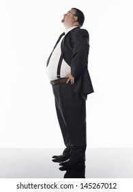 Full length side view of an overweight businessman standing against white background