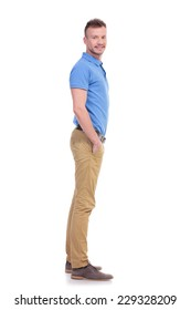 full length side view picture of a young casual man looking into the camera while holding his hands inside his pockets and smiling. isolated on a white background