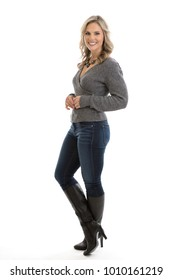 Full length side view portrait of a beautiful mid 30s blond woman wearing a sweater, jeans and high heel boots isolated on a white background