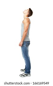 Full length side view portrait of young man looking up isolated on white background