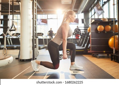 Full length side view portrait of sportive young woman doing squats with weights during workout in sunlit gym, copy space
