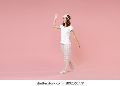 Full length side view portrait funny young woman in white pajamas home wear sleep mask waving greeting with hand as notices someone rest at home isolated on pink background. Relax good mood concept