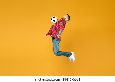 Full length side view portrait of cheerful young man football fan in red shirt cheer up support favorite team with soccer ball jumping isolated on yellow background. People sport leisure concept