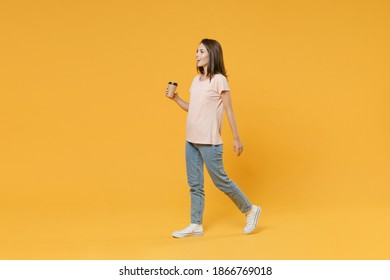 Full length side view portrait of cheerful funny young woman wearing pastel pink casual t-shirt hold paper cup of coffee or tea walking going looking aside isolated on yellow color background studio