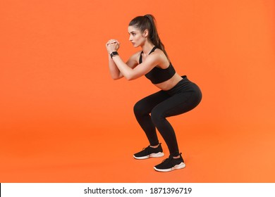 Full length side view portrait strong young fitness sporty woman in black sportswear training working out doing exercise squatting hold hands folded looking aside isolated on orange background studio