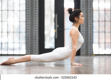 Full length side view portrait of beautiful young woman working out in luxury fitness center, doing yoga or pilates exercise without mat on wooden floor. Upward facing dog, Urdhva mukha svanasana