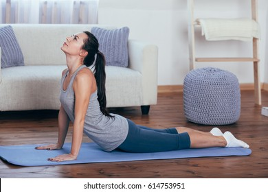 Full length side view portrait of beautiful young woman working out at home, doing yoga or pilates exercise on wooden floor