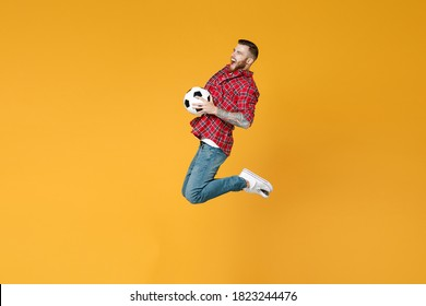 Full length side view of screaming excited young man football fan in red shirt cheer up support favorite team hold soccer ball jumping isolated on yellow background studio People sport leisure concept