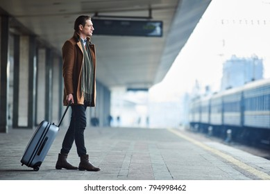 Full length side view serene tourist holding luggage while situating at railway station. Journey concept. Copy space