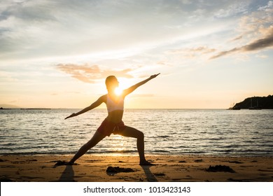 Full length side view of the silhouette of a fit woman practicing the warrior yoga pose against sky at sunset during summer vacation in Flores Island, Indonesia