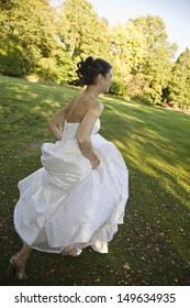 Full length side view of a smiling bride running in park