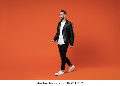 Full length side view of smiling cheerful young bearded man 20s wearing basic white t-shirt black leather jacket standing walking going looking aside isolated on orange background studio portrait
