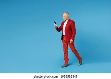 Full length side view of smiling elderly gray-haired mustache bearded business man wearing red jacket suit using mobile cell phone typing sms message isolated on blue color background studio portrait