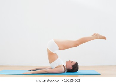Full length side view of a sporty young woman doing posture on exercise mat