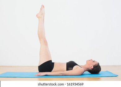 Full length side view of a sporty young woman stretching legs upwards in fitness studio