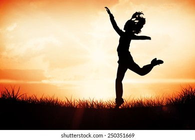 Full length side view of a sporty young blond jumping against orange sunrise