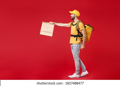 Full length side view step delivery employee man male in yellow cap t-shirt thermal backpack hold craft paper food takeaway bag work courier service in quarantine covid-19 isolated on red background