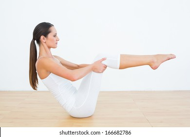 Full length side view of a toned young woman doing the boat pose in fitness studio