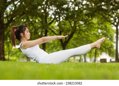 Full length side view of toned young woman doing the boat pose in park
