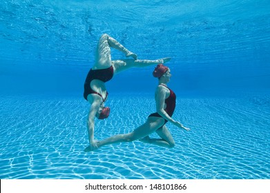 Full length side view of two synchronized swimmers performing underwater