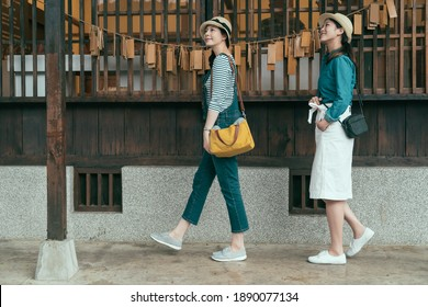full length side view of two asian attractive girl travelers walk in line and looking side during sightseeing in temple. beautiful ladies enjoy sunny day visiting japanese traditional wooden house