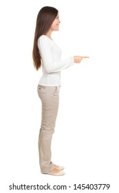 Full length side view of young woman pointing at copyspace isolated over white background