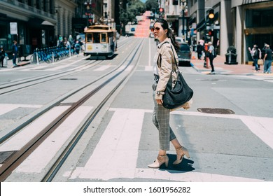 full length side view of young pretty stylish asian chinese female crossing zebra road of san francisco usa. historic cable cars riding on famous california street at dawn on sunny day in busy urban