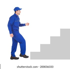 Full length side view of young male cleaner walking isolated over white background