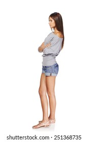 Full length side view of young stylish slim tanned female in denim shorts standing with folded hands looking forward seriously, isolated on white background