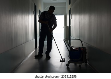Full length of silhouette man with broom cleaning office corridor