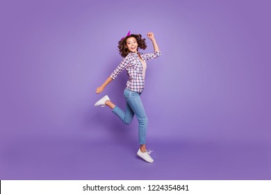 Full length size beautiful attractive dreamy carefree careless lifestyle lady with her modern brunette curly hairdo she run isolated on bright purple background in checkered shirt denim casual jeans
