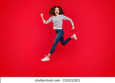 Full length size body photo of fly high pretty charming she her girl going to mall quickly wearing white casual striped sweater denim jeans on red vivid bright background