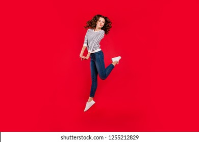 Full length size body photo of jumping high beautiful pretty charming she her girl raised leg fooling send kisses arms together wearing white casual sweater on red vivid bright background