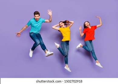 Full length size body photo of two beautiful carefree cheerful excited ladies and one comic funny in blue t-shirt guy waving hand saying hello isolated violet background