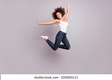 Full length full size fullbody portrait of playful, crazy, childish, funny, pretty, charming positive girl jumpink with hands up, looking at camera, isolated on grey background, having fun
