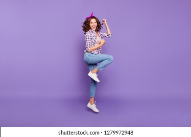 Full length size gorgeous nice adorable good-looking confident lady in checkered shirt with her brunette style stylish trendy curly wave hair she raised fists jump isolated on shine violet background