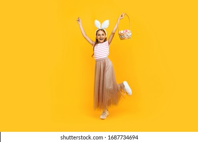 Full length, a small attractive girl on a head with rabbit ears, holding a basket of Easter eggs and showing a victory gesture on a yellow background. Symbol of Easter and spring