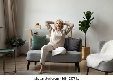 Full length smiling beautiful elderly senior woman sitting on sofa in modern living room, feeling relaxed, enjoying calm weekend leisure time alone at home, happy retirement holiday pastime concept.