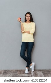 Full length of smiling beautiful young woman standing and holding red apple over grey background