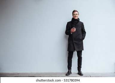 Full length smiling business man in glasses and warm clothes with phone standing near the wall on the street and looking at camera