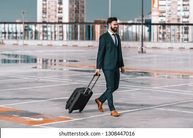 Full length of smiling businessman in formal wear with luggage walking on the parking. Business trip concept.