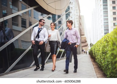 Full length of smiling businesspeople discussing about a meeting while walking in the city.