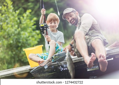 Full length of smiling father and son catching fish in butterfly fishing net