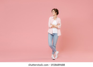 Full length of smiling funny beautiful attractive young woman 20s wearing casual basic checkered shirt holding hands crossed looking aside isolated on pastel pink colour background, studio portrait